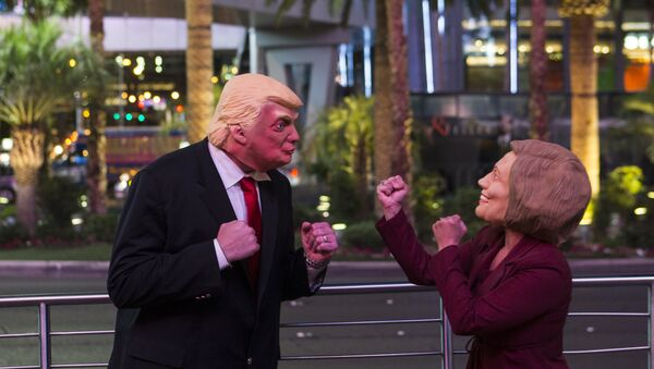 Donald Trump impersonator Rafael Almodovar, left, and Hillary Clinton impersonator Corina Almodovar entertain a crowd as early election results come in from a television display above, Tuesday, Nov. 8, 2016, during election night in Las Vegas - Sputnik International