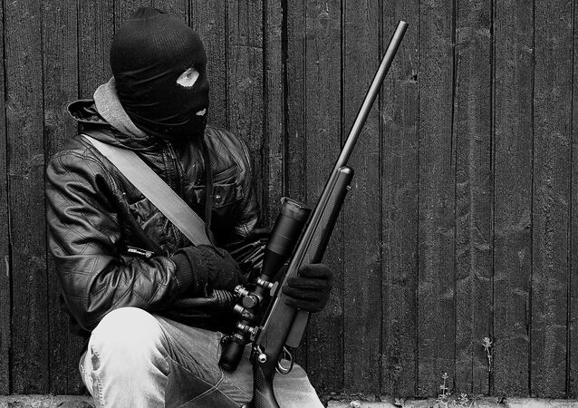 A man wearing a balaclava and holding a weapon