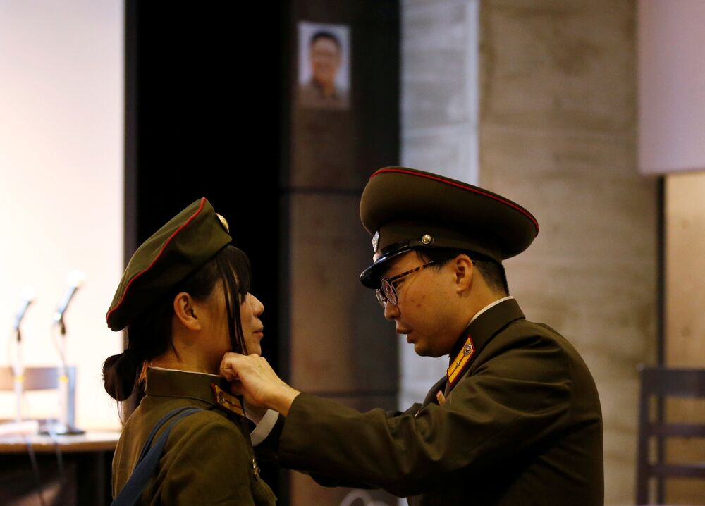 North Korea fans dressed as the Korean People's Army adjust their clothes in front of a portrait of North Korea's late leader Kim Jong Il before a North Korea fan event in Tokyo, Japan October 29, 2017