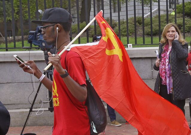 Taizjan Wallace, from the Roxbery section of Boston, carries a Soviet Union hammer & sickle flag in front of the Statehouse after a M1 Coalition Here to Stay May Day Immigration rally which he did not participate in Monday, May 1, 2017, in Boston
