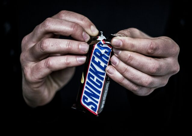 A man opens a Snickers chocolate bar on February 23, 2016 in Lyon, central eastern France