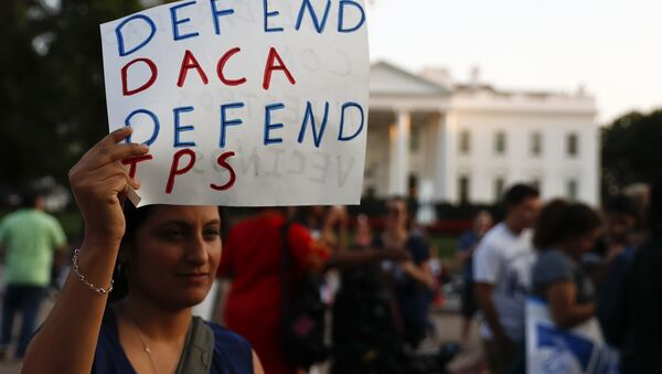A woman holds up a sign that reads Defend DACA Defend TPS during a rally supporting Deferred Action for Childhood Arrivals, or DACA, outside the White House in Washington, Monday, Sept. 4, 2017 - Sputnik International
