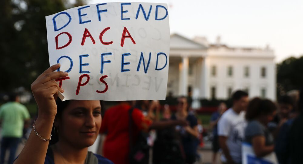 A woman holds up a sign that reads Defend DACA Defend TPS during a rally supporting Deferred Action for Childhood Arrivals, or DACA, outside the White House in Washington, Monday, Sept. 4, 2017