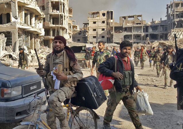 Syrian soldiers, and pro-government forces, are seen in front of damaged buildings in the eastern Syrian city of Deir Ezzor on November 3, 2017