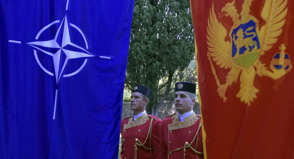 Montenegrin guards of honor stand between NATO, left, and Montenegro flags during ceremony to mark Montenegro's accession to NATO, in Podgorica, Montenegro, Wednesday, June 7, 2017