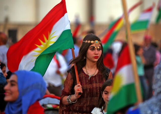 Syrian Kurds wave the Kurdish flag in celebration, in the northeastern Syrian city of Qamishli on September 26, 2017, in support of the independence referendum in Iraq's autonomous northern Kurdish region
