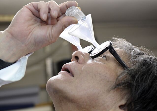 Kenji Kawakami, inventor and founder of the International Chindogu Society demonstrates his funnel glasses designed to guide eyedrops so that they never miss their mark in Tokyo on June 3, 2009