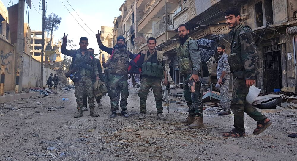 Syrian soldiers, and pro-government forces, pose for a picture in front of damaged buildings in the eastern Syrian city of Deir Ezzor on November 3, 2017
