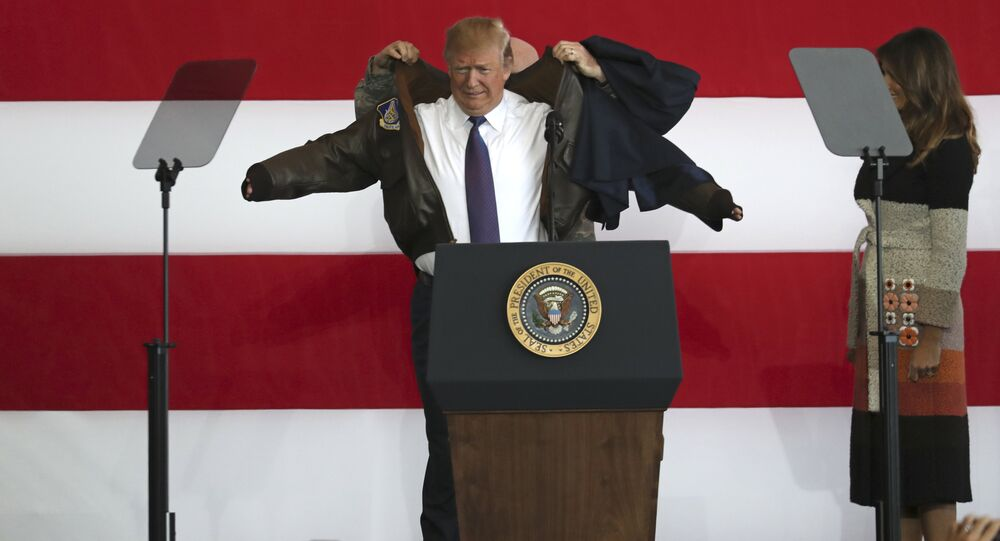 U.S. President Donald Trump, center, puts on a jacket beside first lady Melania Trump, as President Trump meets the US troops at the U.S. Yokota Air Base, on the outskirts of Tokyo, Sunday, Nov. 5, 2017.