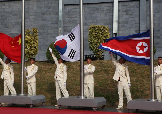 The flags of South Korea (C), China (L) and North Korea (File)