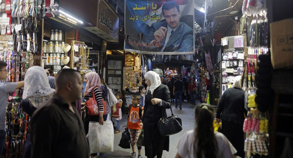 In this May 18, 2017 photo, Syrians shop under a banner showing President Bashar Assad at the Hamadiyah market, in the Old City of Damascus, Syria.