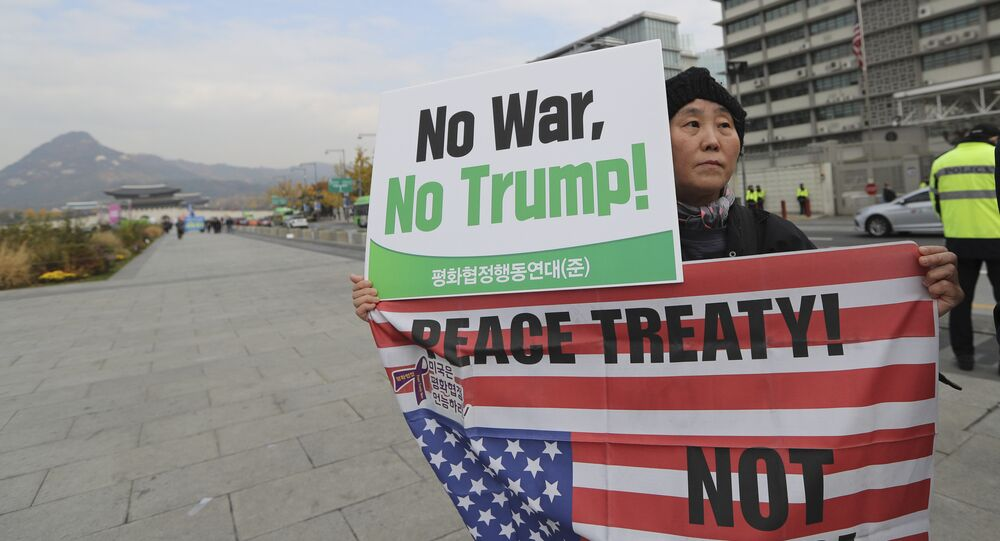 A South Korean woman holds banner during an anti-war rally ahead of U.S. President Donald Trump's visit to the country near U.S. Embassy in Seoul, South Korea, Monday, Nov. 6, 2017