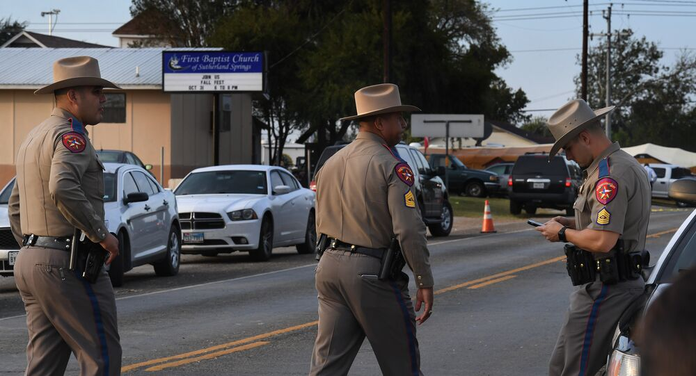 State troopers patrol at the entrance to the First Baptist Church (back) after a mass shooting that killed 26 people in Sutherland Springs, Texas on November 6, 2017