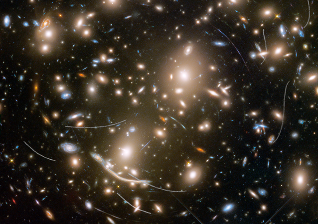 Galaxy cluster Abell 370 contains several hundred galaxies locked together by gravitational pull. It is located approximately 4 billion light-years away in the constellation Cetus, the Sea Monster. The thin, white trails that look like curved or S-shaped streaks are from asteroids that reside, on average, only about 160 million miles from Earth.