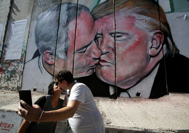Tourists kissing in front of Trump-Netanyahu Mural