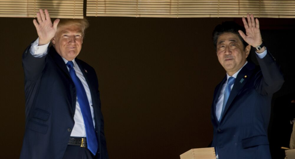 President Donald Trump and Japanese Prime Minister Shinzo Abe wave to members of the media after feeding fish at a koi pond at the Akasaka Palace, Monday, Nov. 6, 2017, in Tokyo.