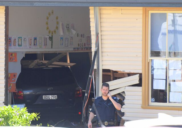 A policeman talks on a phone in front of a vehicle that crashed into a primary school classroom in the Sydney suburb of Greenacre in Australia, November 7, 2017