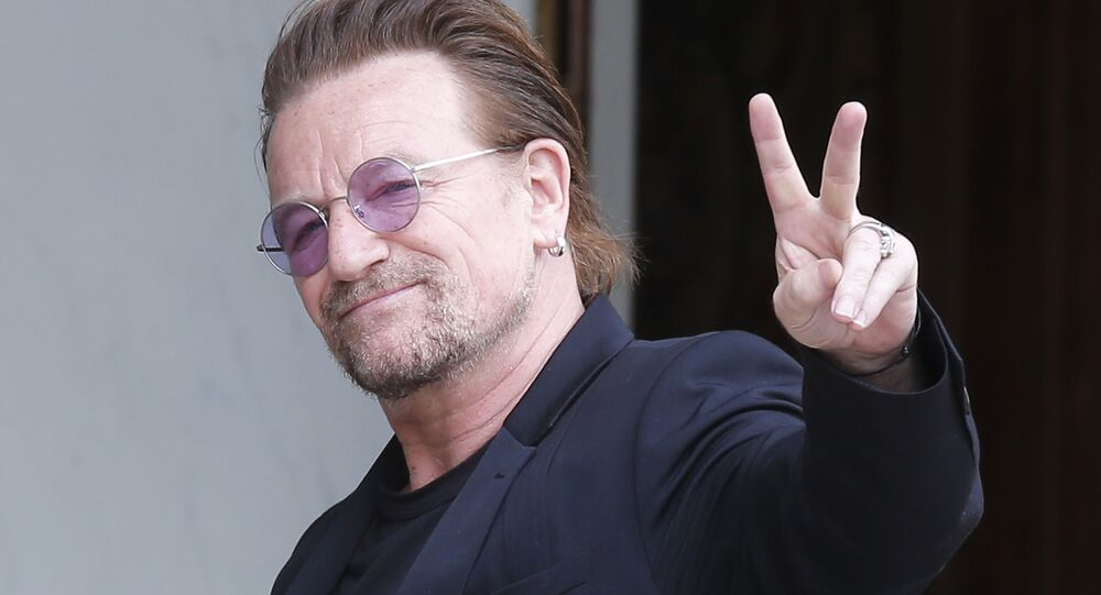 In this Monday, July 24, 2017 file photo, U2 singer Bono makes a peace sign as he arrives for a meeting at the Elysee Palace, in Paris, France.