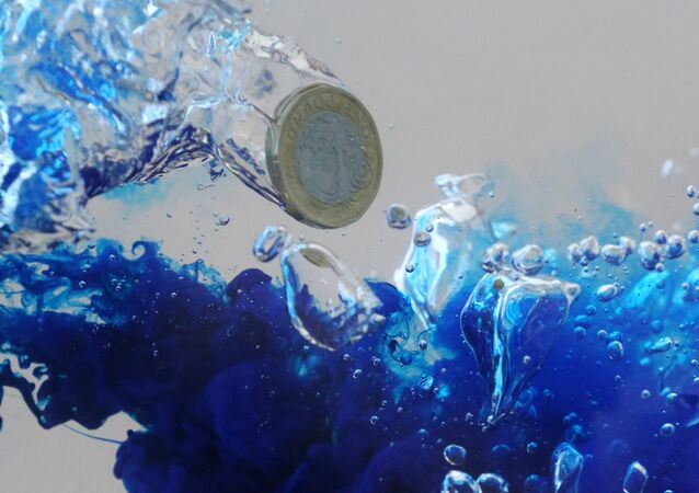 UK pound coin plunges into water in this illustration picture, October 26, 2017. Picture taken October 26, 2017.