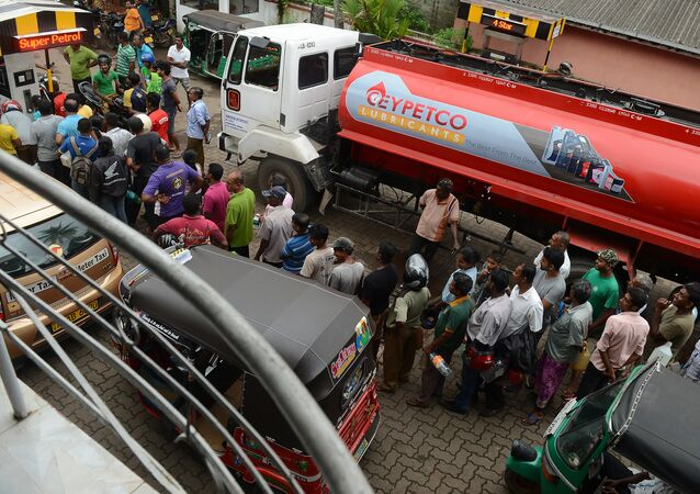 Sri Lankan commuters queue to buy petrol in Colombo on November 6, 2017