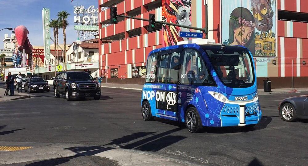 A driverless shuttle bus rolls down a street in Las Vegas