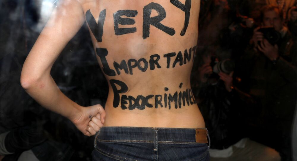 A feminist protester from the Femen group reveals messages written on her body upon the arrival of director Roman Polanski at an event organised by Cinematheque Francaise in Paris, France, October 30, 2017.