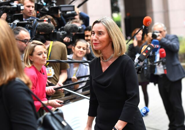 EU's High representative for foreign affairs and security policy Federica Mogherini (R) waves as she arrives in Brussels, on October 19, 2017