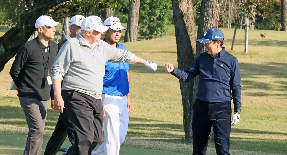 U.S. President Donald Trump gestures to Japan's Prime Minister Shinzo Abe as Japanese professional golfer Hideki Matsuyama looks on, as they play golf at the Kasumigaseki Country Club in Kawagoe, north of Tokyo, Japan, in this photo taken and released by Japan's Cabinet Public Relations Office via Kyodo November 5, 2017