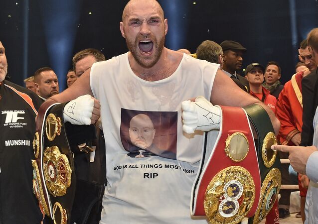 In this Nov. 29, 2015 file photo, Britain's new world champion Tyson Fury, celebrates with the WBA, IBF, WBO and IBO belts after winning the world heavyweight title fight against Ukraine's Wladimir Klitschko in Duesseldorf, western Germany.