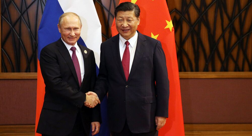 Russian President Vladimir Putin and Chinese President Xi Jinping shake hands during a meeting on the sidelines of the APEC summit in Danang, Vietnam