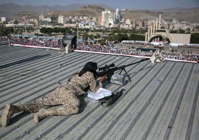 A Houthi Shiite sniper keeps watch over a rally to mark the third anniversary of the Houthis' takeover of the Yemeni capital, in Sanaa.