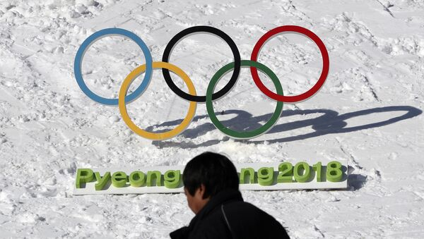 In this Feb. 3, 2017 photo, a man walks by the Olympic rings with a sign of 2018 Pyeongchang Olympic and Paralympic Winter Games in Pyeongchang, South Korea - Sputnik International