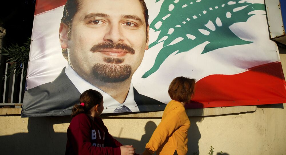 A woman and her daughter pass by a poster of outgoing Prime Minister Saad Hariri, in Beirut, Lebanon, Saturday, Nov. 11, 2017. Lebanon's president has called on Saudi Arabia to clarify the reasons why the country's prime minister has not returned home since his resignation which was announced from the kingdom