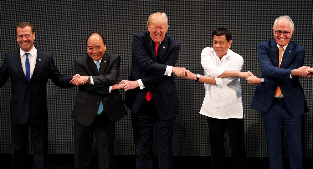 U.S. President Donald Trump smiles with other leaders, including Russia's Prime Minister Dmitry Medvedev, Vietnam's Prime Minister Nguyen Xuan Phuc, President of the Philippines Rodrigo Duterte and Australia's Prime Minister Malcolm Turnbull, as they cross their arms for the traditional ASEAN handshake in the opening ceremony of the ASEAN Summit in Manila, Philippines November 13, 2017
