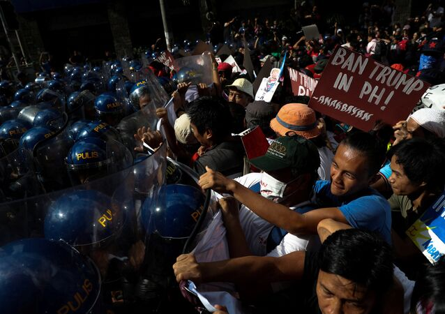 Protesters clash with anti-riot police officers as they try to march towards the U.S. embassy during a rally against U.S. President Donald Trump's visit, in Manila, Philippines, November 12, 2017