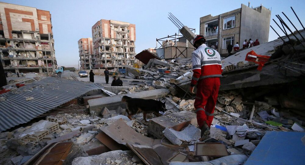 In this photo provided by the Iranian Students News Agency, ISNA, a rescue worker searches debris for survivors with his sniffing dog after an earthquake at the city of Sarpol-e-Zahab in western Iran, Monday, Nov. 13, 2017