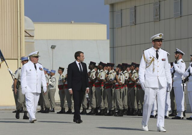 French President Emmanuel Macron reviews the French honor guard at the naval base during his second day of visit in Abu Dhabi, United Arab Emirates, Thursday, Nov. 9, 2017