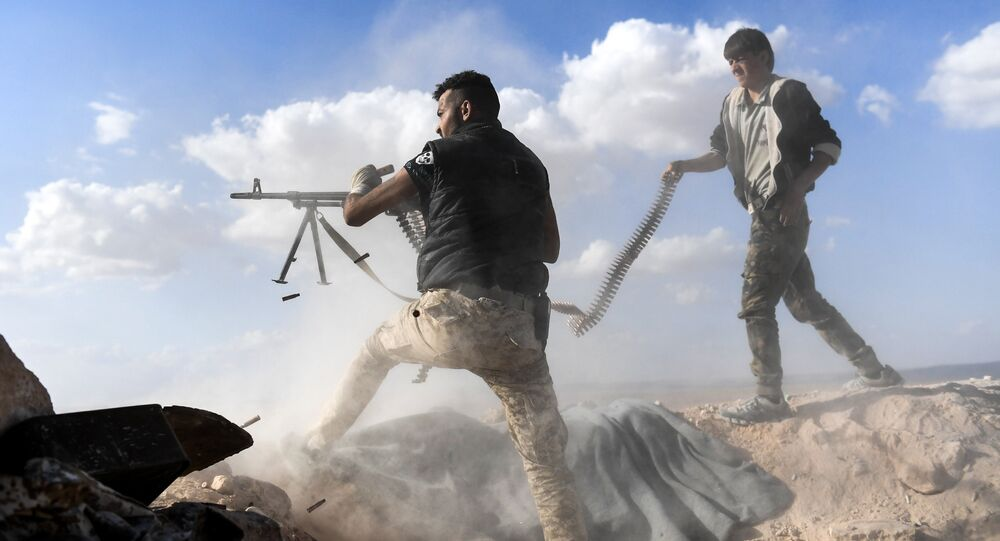 A member of the Syrian pro-regime forces fires a machine gun as a comrade holds his feeding ammunition belt, during the advance towards rebel-held positions west of Aleppo, near Abu al-Zuhur military airport in the Idlib province countryside, on November 11, 2017