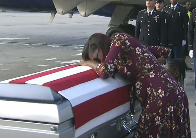 Myeshia Johnson cries over the casket of her husband, Sgt. La David Johnson, who was killed in an ambush in Niger, upon his body's arrival in Miami