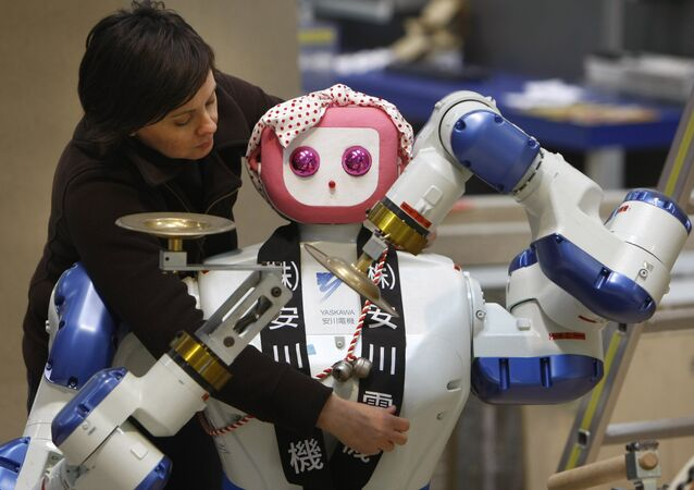 Annette Vorreiter decorates a dual arm robot maid by Japan's Yaskawa Electric company during preparation of the Hanover industrial fair in Hanover, Germany, Friday, April 18, 2008