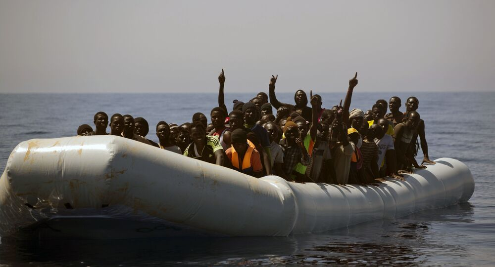 Migrants and refugees call out to Spanish NGO Proactiva Open Arms workers, after being located out of control sailing on a rubber boat in the Mediterranean Sea, about 18 miles north of Sabratha, Libya
