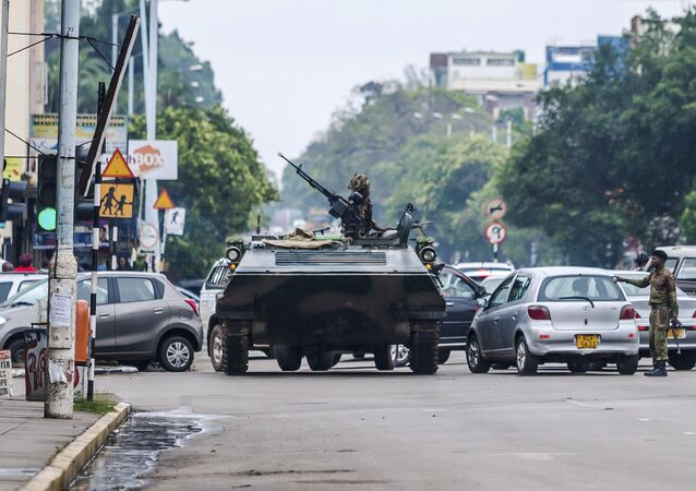 An armoured personnel carrier stations by an intersection as Zimbabwean soldiers regulate traffic in Harare on November 15, 2017