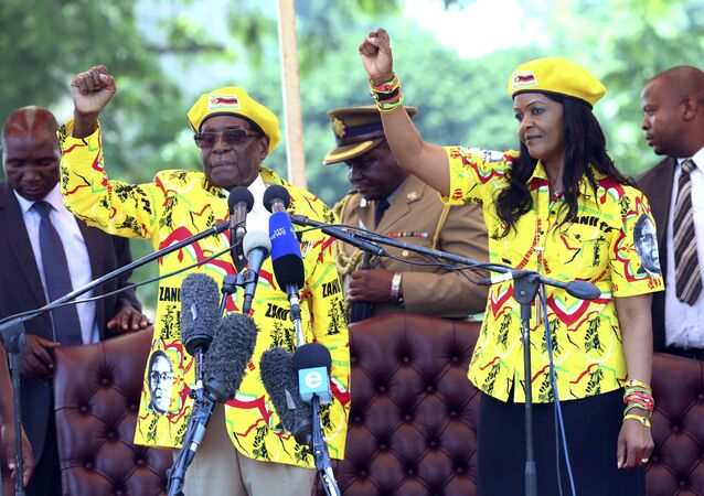 In this Nov. 8, 2017, file photo, Zimbabwe's President Robert Mugabe, left, and his wife Grace Mugabe chant the party's slogan during a solidarity rally in Harare, Zimbabwe.