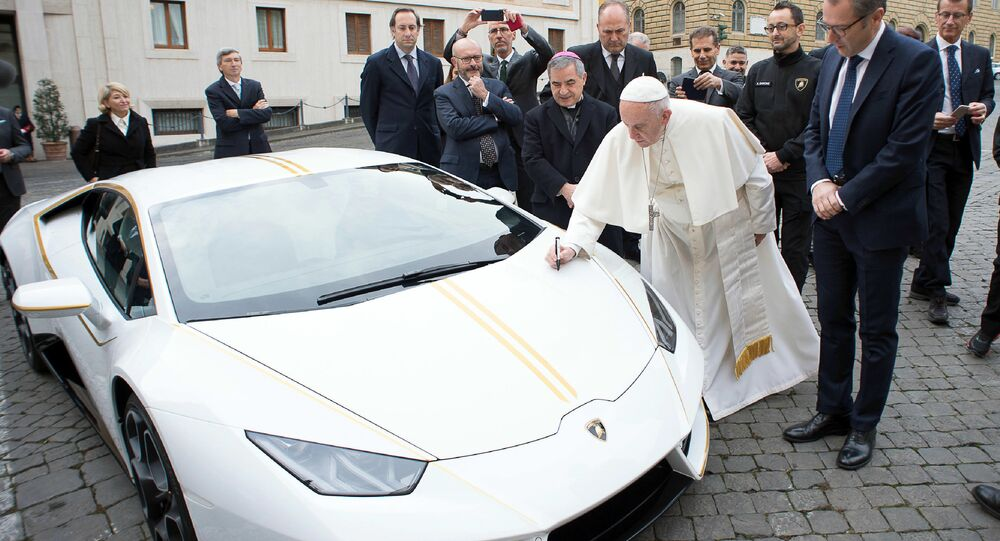 Pope Francis writes on the bonnet of a Lamborghini donated to him by the luxury sports car maker, at the Vatican