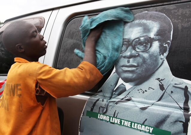 Youth washes a minibus adorned with picture of President Robert Mugabe at a bus terminus in Harare, Zimbabwe, November 15, 2017