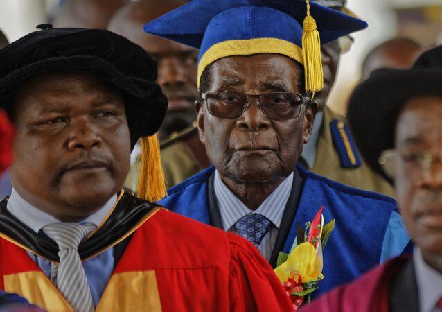 Zimbabwe's President Robert Mugabe, center, arrives to preside over a student graduation ceremony at Zimbabwe Open University on the outskirts of Harare, Zimbabwe Friday, Nov. 17, 2017