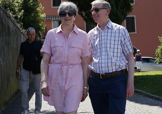 Britain Prime Minister Theresa May, left, walks with her husband Philip as they visit Desenzano del Garda, by the Garda lake, northern Italy, Tuesday, July 25, 2017. May is spending her holidays in northern Italy.