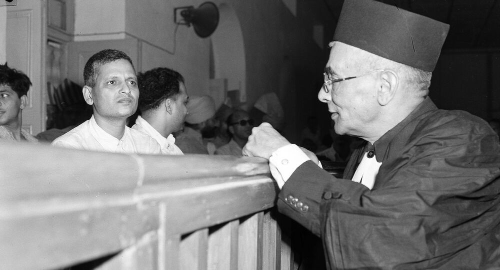 Nathuram Godse, left, one of nine co-defendants in the Mohandas Gandhi assassination conspiracy case, and defense counsellor L.B. Bhopatkar confer May 27, 1948, at the start of the hearing