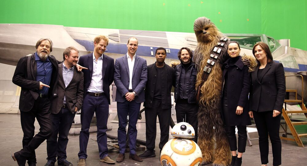 US actor Mark Hamill, US director Rian Johnson, Britain's Prince Harry, Britain's Prince William, British actor John Boyega, character Chewbacca and British actress Daisy Ridley, from left, and droid BB-8 pose for a photo during a tour of the Star Wars sets at Pinewood studios in Iver Heath, west London, Tuesday April 19, 2016