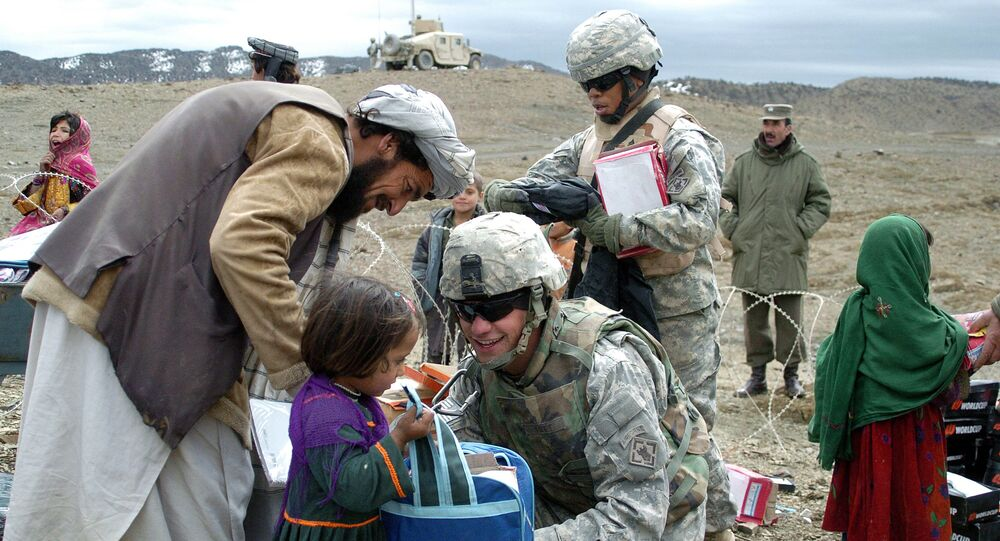 In this US Miltary Handout picture taken, 16 March 2007, U.S soldiers with the NATO-led International Security Assistance Force (ISAF) distribute school stationery to Afghan children in Orgun in eastern Afghanistan